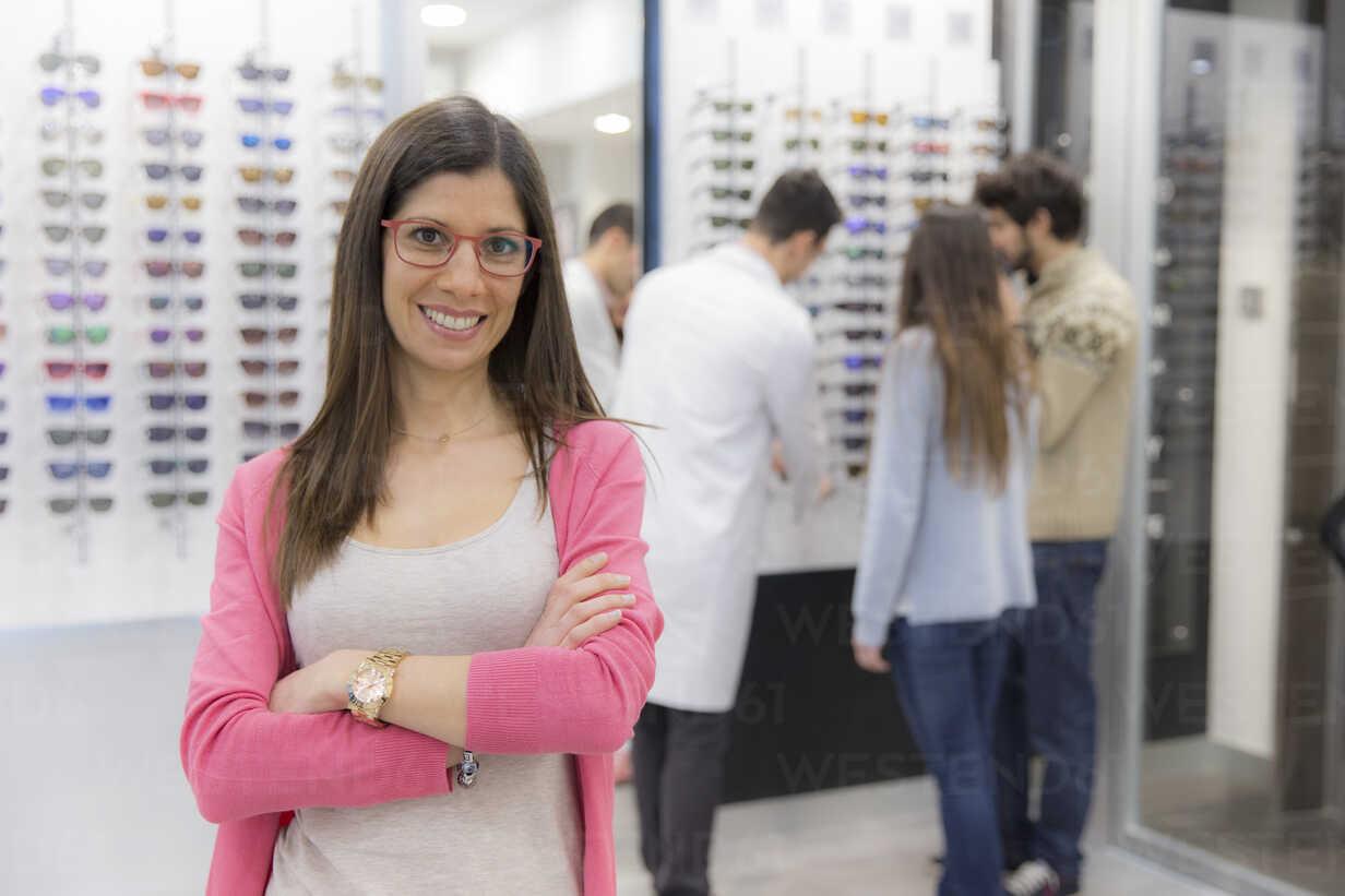 Porträt einer lächelnden Frau in einem Optikergeschäft mit Menschen im Hintergrund - ERLF000140 - Enrique Ramos/Westend61