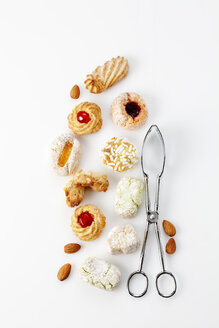 Different sorts of Italian almond cookies, pastry tong  and almonds on white background - CSF027230