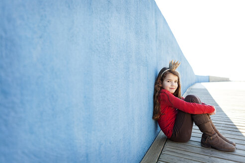 Portrait of little girl with a crown leaning against blue wall - VABF000207