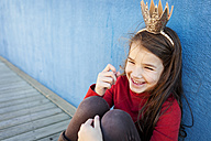Portrait of laughing little girl with a crown leaning against blue wall - VABF000210