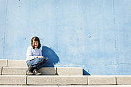 Portrait of smiling little girl sitting on steps in front of blue wall - VABF000216