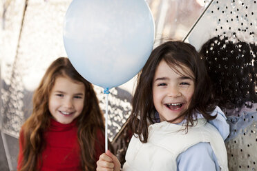 Portrait of laughing little girl with balloon and sister in the background - VABF000218