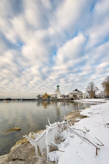 Germany, Wasserburg, Lakeshore with frozen branch and St George's Church in background - SH001900