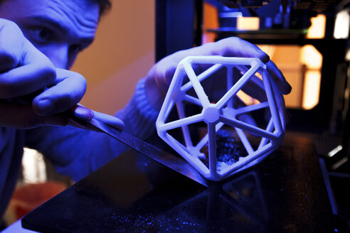 Man using a spatula to separate a 3D geometric figure from the platform of a 3D printer - ABZF000220