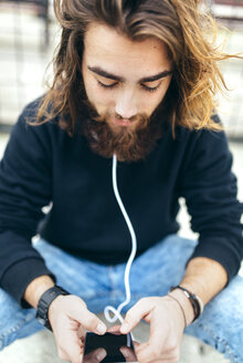 Bearded young man looking at his smartphone - MGOF001458