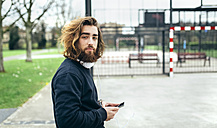 Portrait of bearded young man with smartphone and headphones - MGOF001461