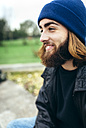 Portrait of smiling young man wearing blue woolly hat - MGOF001464