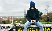 Bearded young skateboarder sitting on a wall looking at his smartphone - MGOF001470