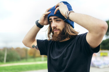 Portrait of bearded young man putting on his woolly hat - MGOF001473