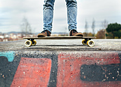 Legs of young man standing on his skateboarder - MGOF001476