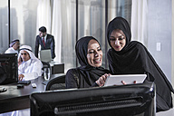 Middle Eastern businesswomen in office looking at digital tablet - ZEF008581