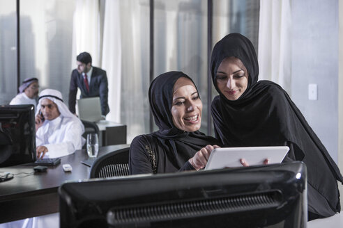Middle Eastern businesswomen in office looking at digital tablet - ZEF008581