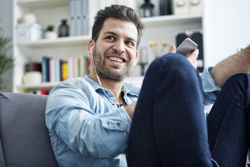 Happy young man at home with smartphone and earbuds - SEGF000442