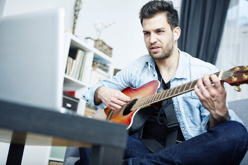 Young man at home sitting on couch playing guitar and looking at laptop - SEGF000451