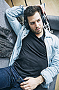 Young man at home lying on couch wearing headphones - SEGF000457