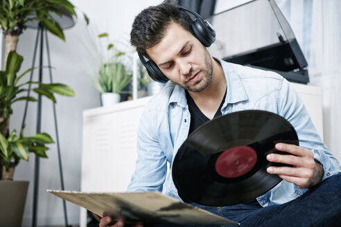 Young man wearing headphones looking at record - SEGF000460