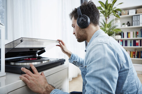 Young man wearing headphones starting record player - SEGF000466