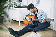 Young man sitting on floor playing guitar - SEGF000469
