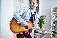Happy young man at home playing guitar - SEGF000478