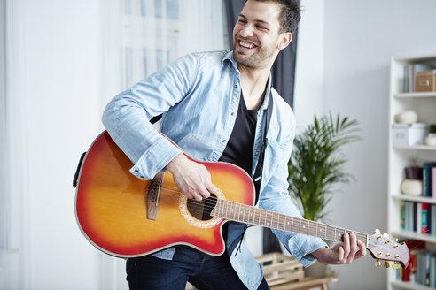 Happy young man at home playing guitar - SEGF000478