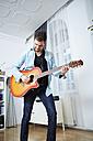 Young man at home playing guitar - SEGF000481