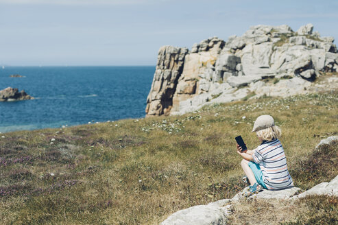 France, Brittany, Cote de Granit Rose, boy sitting at the coast with cell phone - MJF001764