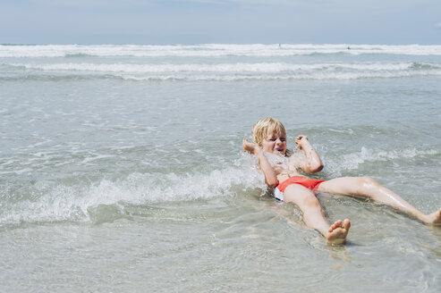France, Brittany, Finistere, Pointe de la Torche, boy lying in water - MJF001782