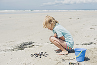 France, Brittany, Finistere, Pointe de la Torche, boy playing with seashells on the beach - MJF001785