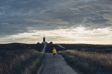 France, Brittany, Pointe du Raz, boy walking towards lighthouses Phare de la Vieille and Phare de Tevennec - MJF001797