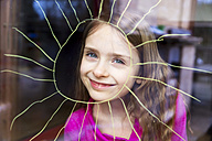 Portrait of smiling girl looking through windowpane with painted sun - SARF002588