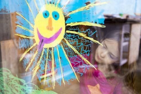 Girl painting sun on windowpane - SARF002591