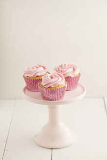 Three pink cup cakes on a cakestand - ECF001848