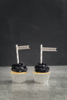 Two cup cakes with black coloured buttercream topping and pennons - ECF001860