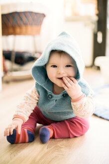 Portrait of smiling baby girl wearing hooded jacket sitting on the floor with finger in mouth - BRF001256