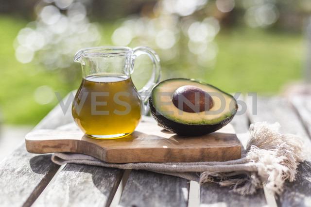 Half of avocado and glass jug of avocado oil on wooden board - SARF002593