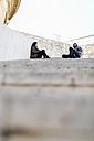 Spain, Tarragona, city break, young couple talking, sitting on steps - JRFF000458