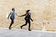 Spain, Tarragona, Young couple running - JRFF000461