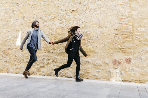 Spain, Tarragona, Young couple running - JRFF000461