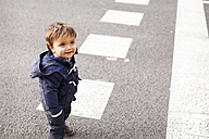 Portrait of smiling little boy standing on a road looking up - VABF000228
