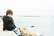 Portrait of little boy sitting on a wall in front of the sea - VABF000231