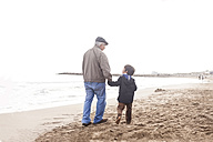 Grandfather and grandson walking and talking on the beach - VABF000246