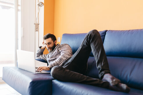 Bearded young man working at home relaxed lying on the couch, using laptop - JRFF000473