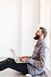 Bearded young man working at home relaxed, sitting on the floor, using laptop - JRFF000479