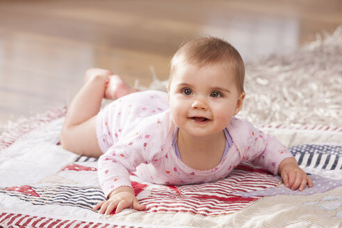 Portrait of baby girl lying on a blanket on the floor - DSF000625