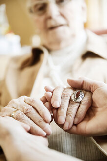Adult daughter holding hands of her mother with Alzheimer's disease, close-up - JATF000846
