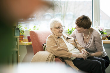 Adult daughter talking to her mother with Alzheimer's disease in her room at retirement home - JATF000849
