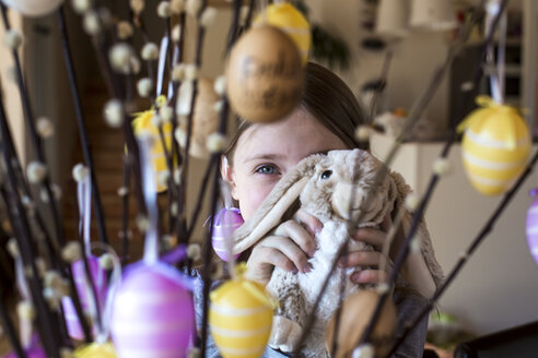 Girl hiding behind Easter bunny and twigs of pussy willows decorated with Easter eggs - SARF002605