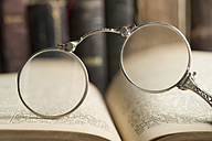 Lorgnette in front of antique books - CRF002738