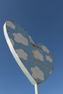 Rusty light blue metal heart with white clouds in front of blue sky - VIF000471