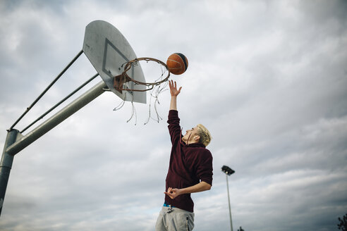 Young man playing basketball on an outdoor court - JRFF000481
